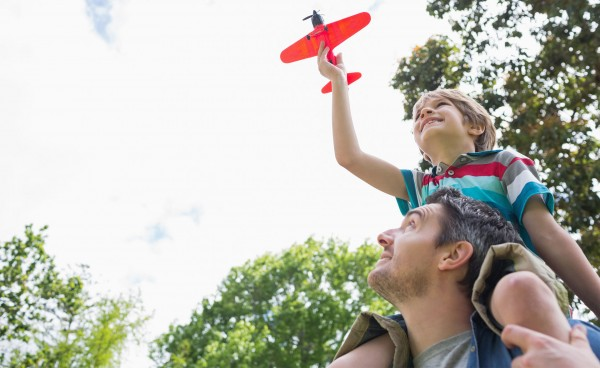 father and son playing with toy plane with son on father's shoulders